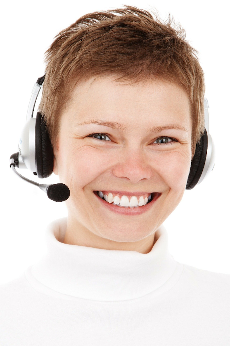 A smiling female wearing a headset with microphone