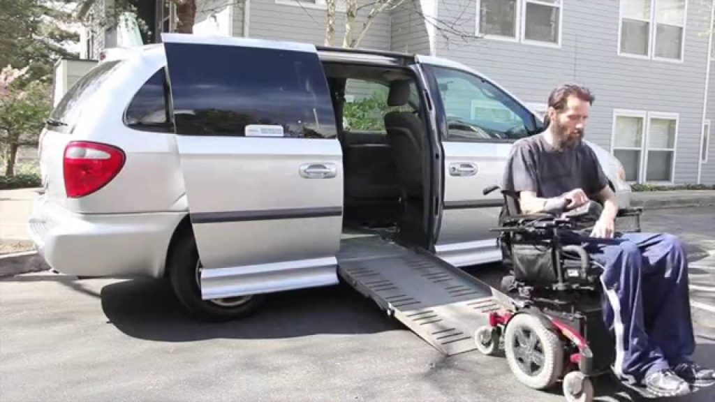Man in motorized wheelchair exiting his accessible minivan