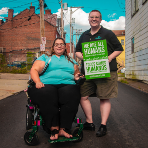 "Woman utilizing a wheelchair stands next to her care provider who is holding a sign that reads ""we are all human"""