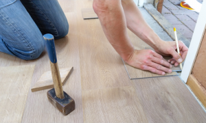 Person installing wood flooring