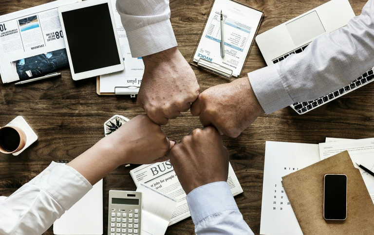Four fists touching each other forming a circle with the background of a table with notepads, calculators, and a tablet
