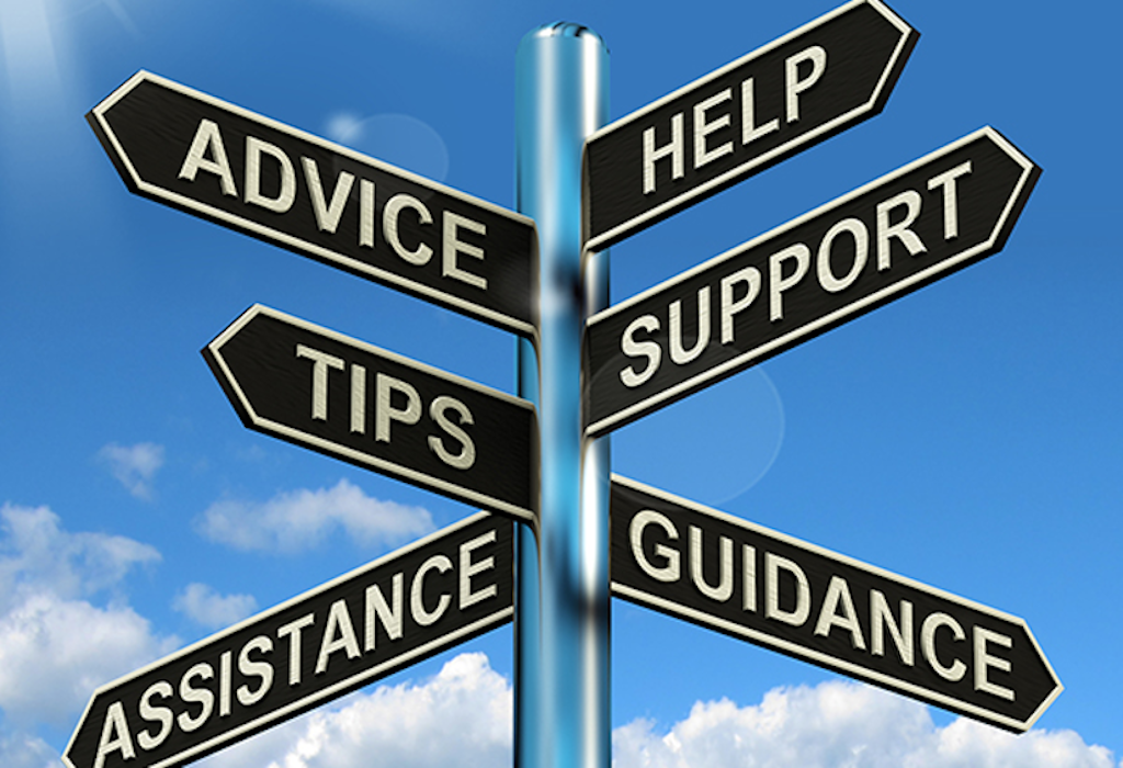 A post with signs pointing in different directions. The signs have the words: help, assistance, support, tips, guidance and assistance