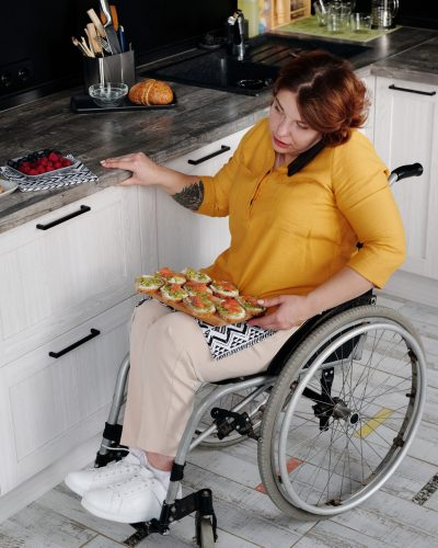 Woman in wheelchair using phone and kitchen and preparing a meal