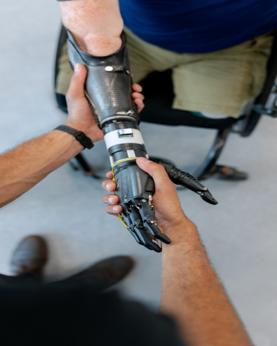 Photo of two individuals shaking hands. One has a prosthetic arm
