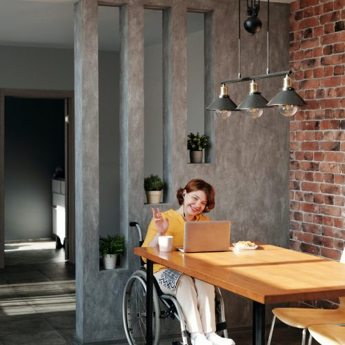 Woman sitting in a wheelchair enjoying a cup of coffee and video chatting